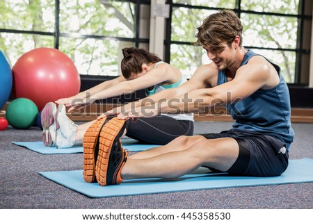 Man and woman performing fitness exercise at gym - stock photo