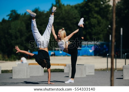 man and woman performing tricks in the park