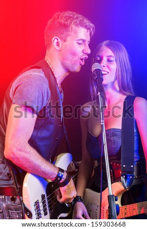 Man and Woman Playing and Singing Rock Music - stock photo