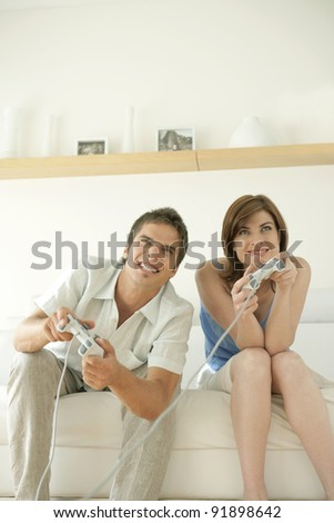 Man and woman playing video games at home.