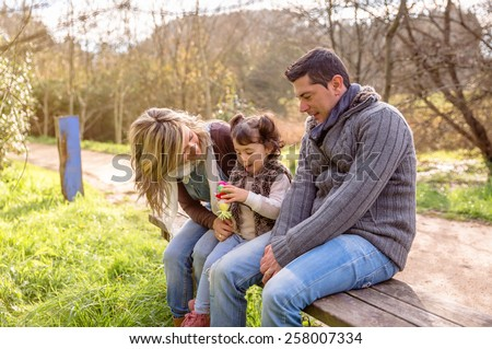 Man and woman playing with a little girl sitting on the center of a wooden bench in the park. Family leisure outdoors concept.