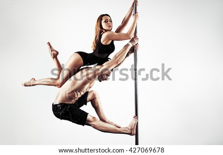 Man and woman pole dance team on white wall background