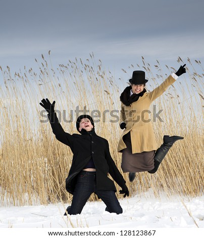 Man and woman posing near winter lake beach