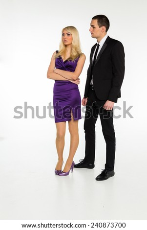 Man and woman posing on a white background. Unhappy girl turned away from the guy. Relationships between people - resentment, betrayal, jealousy, love. - stock photo