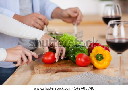 Man and woman preparing a vegetable salad