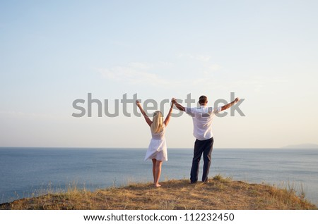 Man and woman raising their hands to the sky while standing on the beach - stock photo