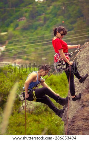 man and woman rapelling down mountain in blue and red clothing - stock photo