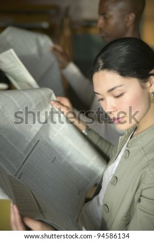 Man and woman reading newspaper - stock photo
