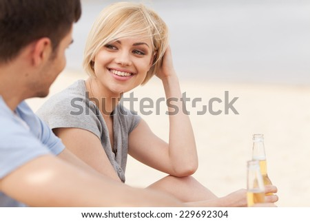 Man and woman relaxing on beach with beer. Happy couple drinking together on beach  - stock photo