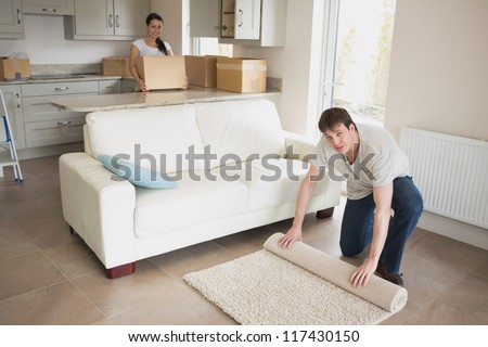 Man and woman relocating and furnishing their new house - stock photo
