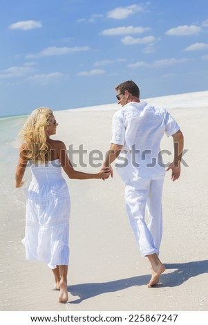 Man and woman romantic couple in white clothes running holding hands on a deserted tropical beach with bright clear blue sky