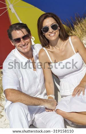 Man and woman romantic couple wearing sunglasses under a multi colored sun umbrella or parasol on a beach