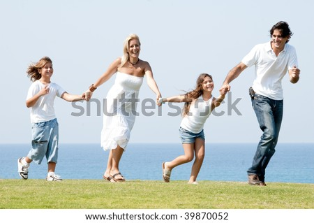 Man and woman running on meadow holding children hands and enjoying - stock photo