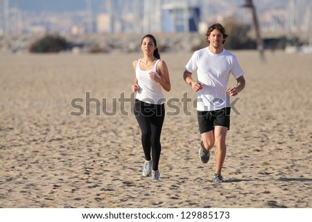 Man and woman running on the beach with an unfocused background