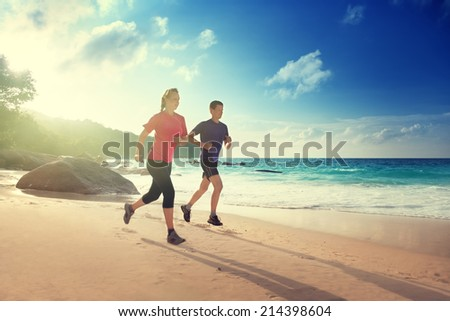 Man and woman running on tropical beach at sunset  - stock photo