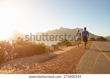 Man and woman running together on an empty road - stock photo