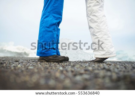 man and woman's feet on black ground by sea