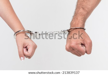 Man and woman's hands handcuffed together concept of love, relationship, romance, sex, crime, punishment, prison isolated on white