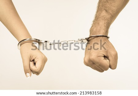 Man and woman's hands handcuffed together concept of love relationship romance sex crime punishment prison isolated on white color toned - stock photo