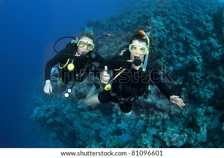 man and woman scuba dive together - stock photo