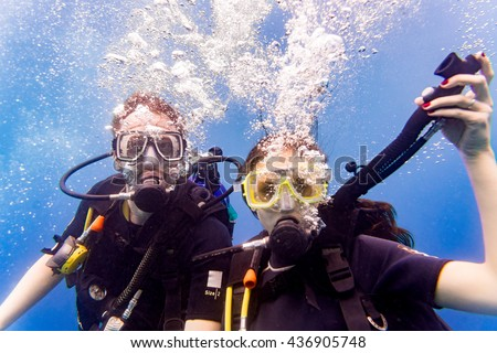 Man and woman scuba divers in tropical sea diving up after underwater excursion  - stock photo