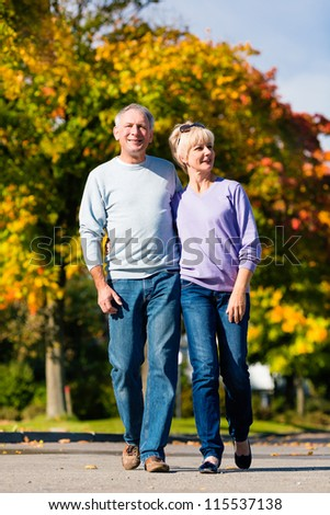 Man and woman, senior couple, having a walk in autumn or fall outdoors, the trees show colorful foliage - stock photo
