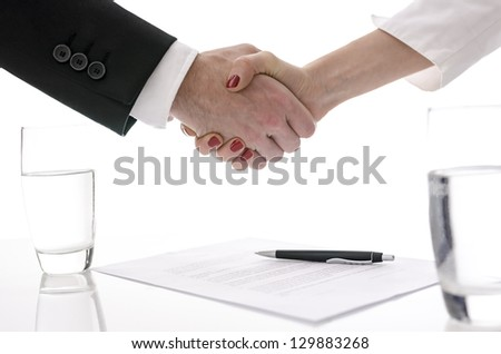 Man and woman shaking hands above table with signed contract. - stock photo