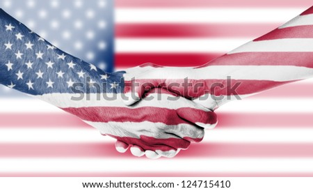 Man and woman shaking hands, arms wrapped in the flag of the USA - stock photo