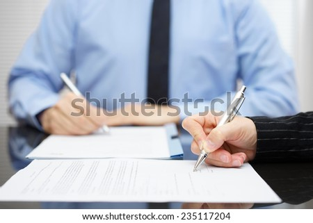 Man and woman   signing a business contract after the conclusion of the negotiations - stock photo