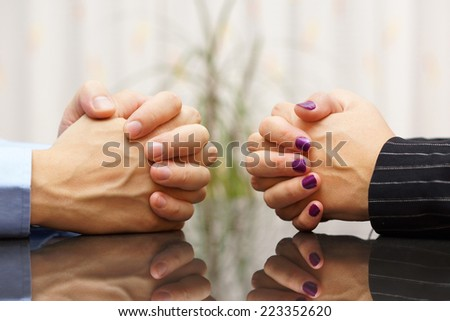 Man and woman sits at a desk with hands clasped. marital problems, conflicts and stubborn concept - stock photo