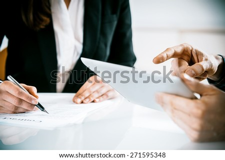 Man and woman sitting at an office table in a business meeting with the woman taking notes as the man points to his tablet, close up of their hands