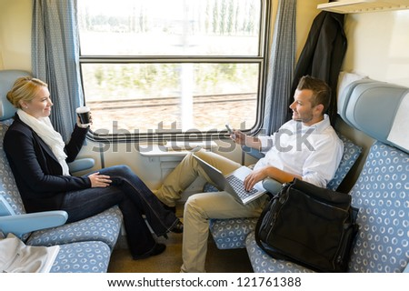 Man and woman sitting in train talking smiling commuters friends - stock photo