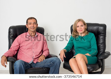 Man and woman sitting on leather chairs