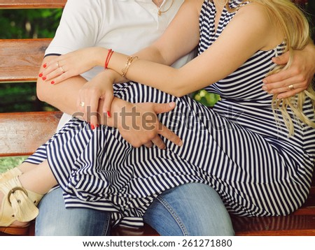 man and woman sitting together on wooden bench - stock photo
