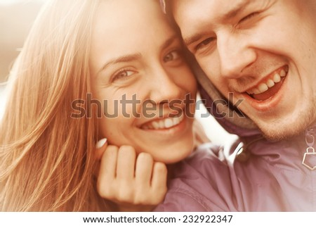 Man and woman smiling and taking pictures of themselves