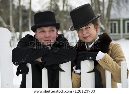 Man and woman stand behind white wooden fence
