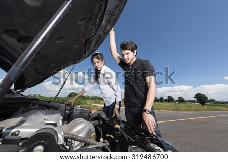 Man and woman stand by the broken car and don't know what to do - stock photo