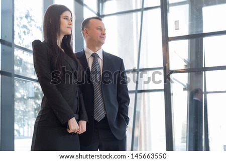 Man and woman stand near the glass windows