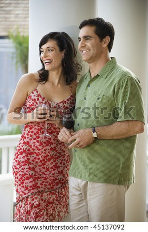 Man and woman stand together with glasses of red wine. Vertical shot. - stock photo