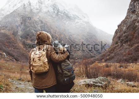 Man and woman standing and hugging by the mountain, winter hike with backpacks