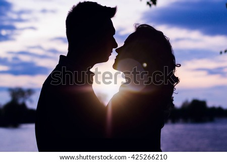 Man and woman standing arm in arm on a rock by the sea  - stock photo