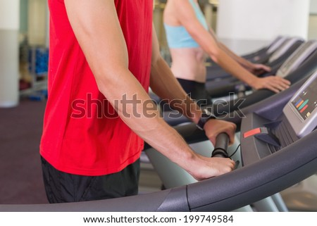 Man and woman standing on treadmills at the gym