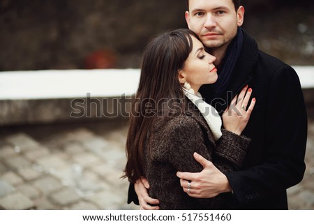man and woman stands and hug each other outdoors
