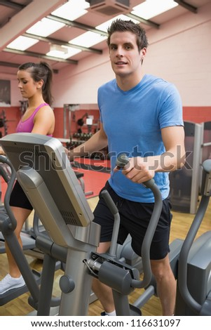 Man and woman stepping on a step machine in gym