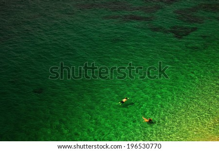 Man and woman swimming in calm sea from birds eye view. Eps10 vector illustration - stock photo