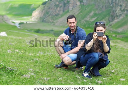 man and woman taking photo with smart phone and camera at mountain peak cliff