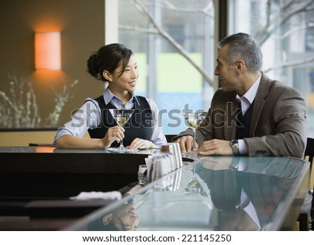 Man and woman talking at bar - stock photo