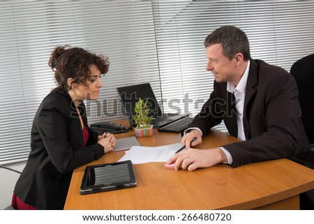 Man and woman talking together looking at document - stock photo