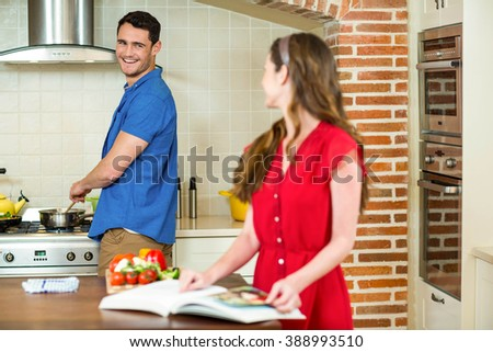 Man and woman talking together while working in kitchen at home - stock photo