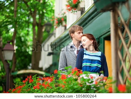 Man and woman together on balconyof their house or hotel with blossoming geranium and nice view - stock photo